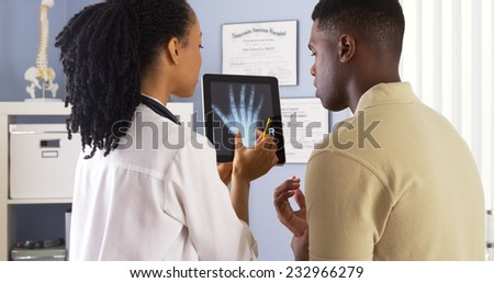 Black female doctor sharing hand x ray with patient on tablet - stock photo