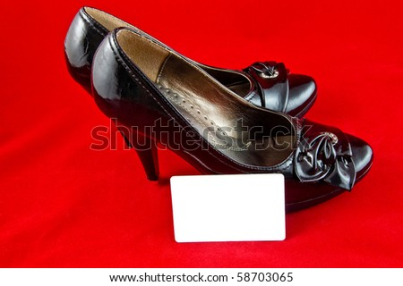 black female shoes with white card on red background