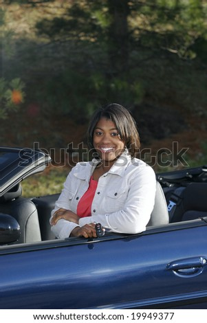 black female teen driver sitting with new carhttp://admin.shutterstock.com/78625/upload2/uploads/small/58695/58695,1225768132,1.jpg - stock photo