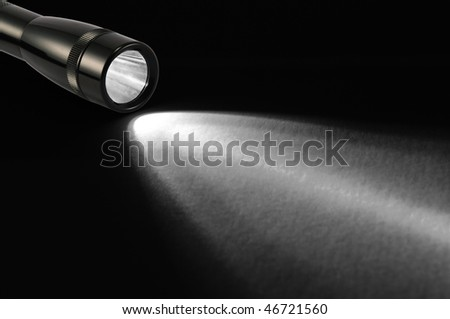 Black flashlight and shaft on black background. - stock photo