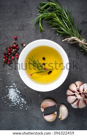 Black food background with olive oil, fresh aromatic herbs and spices, copy space, top view. - stock photo