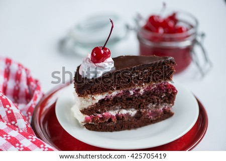 black forest cake, a jar with a cocktail cherry and red napkin - stock photo