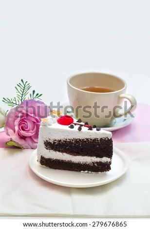 Black Forest Cake and  cherry on top, with cup of tea