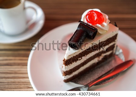 Black forest cake on wood table and coffee background in coffee shop  - stock photo