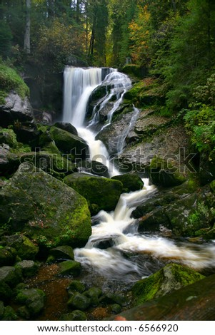 Black Forest Falls: Vertical Shot of a waterfall cascade over moss-covered rocks in the Black Forest, Tribourg, Germany. - stock photo