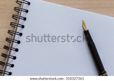 Black Fountain Pen Placed on a Blank Notebook - stock photo