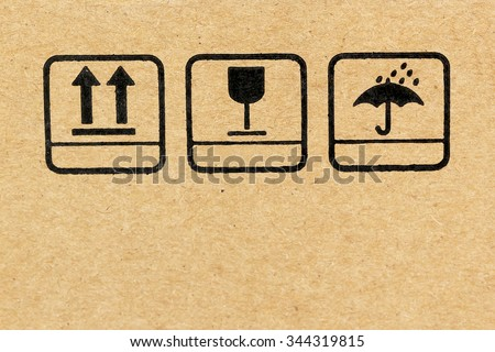 Black fragile symbol on cardboard for packaging 'keep dry' and 'this way up with fragile'