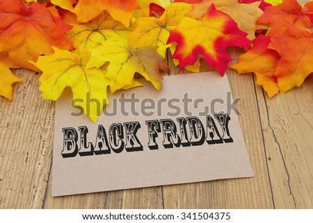 Black Friday Card, Autumn Leaves with a beige greeting card with text Black Friday - stock photo