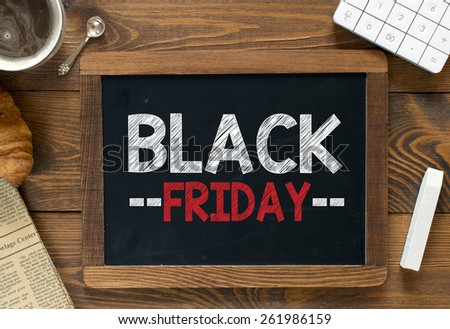 Black friday handwritten on blackboard. Black friday handwritten with white chalk on a blackboard, cup of coffee ,croissant, newspaper and calculator on wooden background - stock photo