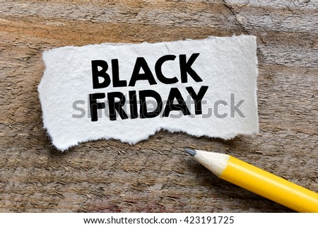 Black friday inscription. Pencil and torn paper with black friday inscription on wooden background - stock photo