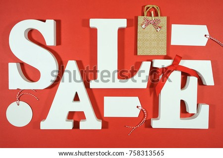 Black Friday or retail sales promotion concept with large white SALE letters flat lay on red background