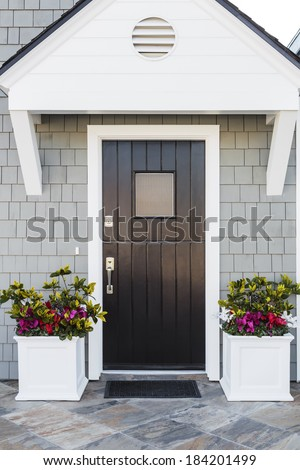 Black front door to a family home; The door is made of vertical wood boards, with a window, framed by two flower planters, gray shingles of the house, and a door mat. Also seen is attic vent detail. - stock photo