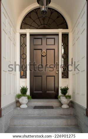 Black Front Door with Lunette and Side Windows in White Arched Entryway with Potted Plants, Doormat and Overhead Hanging Lamp - stock photo
