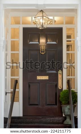 Black Front Door with Surrounding Door Frame of Windows - stock photo