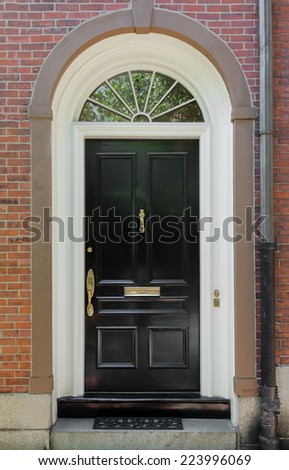 Black Front Door with White Door Frame and Archway Window on a Brick Building - stock photo