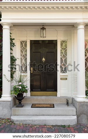 Black Front Door with White Door Frame and Side Windows over Steps with Potted Plant