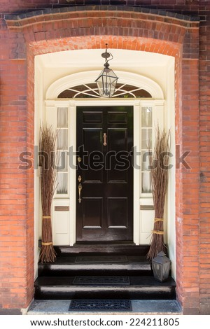 Black Front Door with White Door Frame in Brick Building and Decorative Bunches of Branches  - stock photo