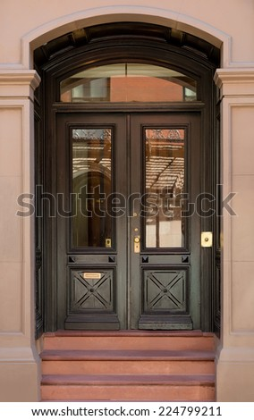 Black Front Double Doors with Crosshatch Detail and Windows - stock photo