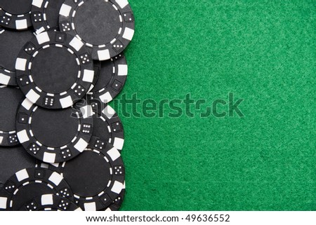Black gambling chips on green felt background with copy space - stock photo