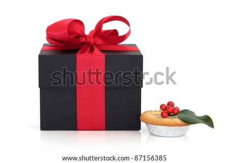 Black gift box with red satin ribbon and bow and christmas mince pie with holly berry leaf sprig isolated over white background. - stock photo
