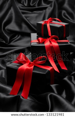 Black gift box with red satin ribbons and bows, over black satin - stock photo