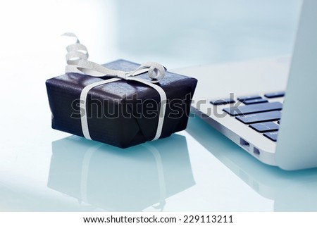 Black gift box with silver bow on light background next to the computer. On line shopping - stock photo