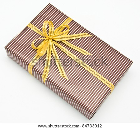 Black gift box with white bar attached gold ribbon on white background.