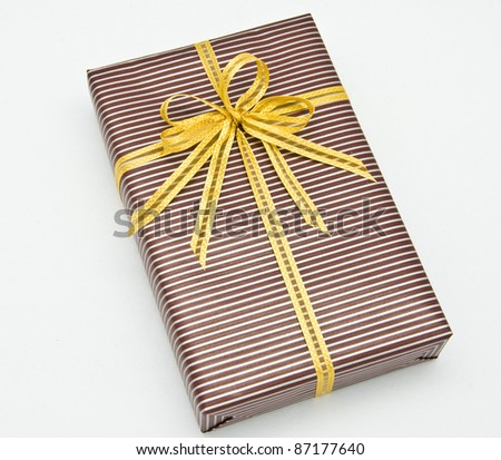 Black gift box with white bar attached gold ribbon on white background. - stock photo