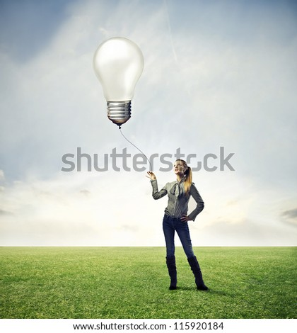 Black girl in a large grace field holding with a wire a big bulb in the air
