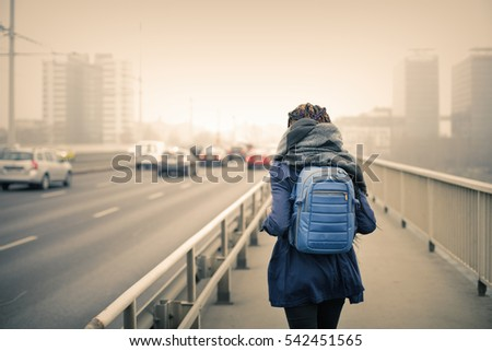 Black girl in blue coat carrying a blue backpack