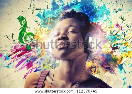 Black girl listening to the music with a pair of headphones - stock photo