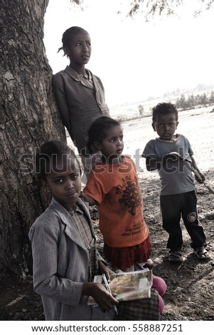 black girl with notebook before school with her family sitting near the tree, december 2015, oromia state, ethiopia