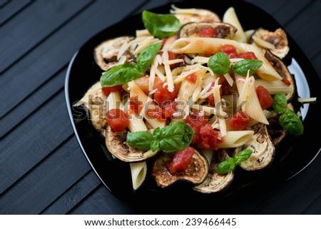 Black glass plate with italian pasta alla Norma, studio shot - stock photo