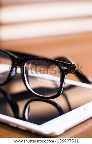 Black glasses and a white tablet on a wooden table - stock photo