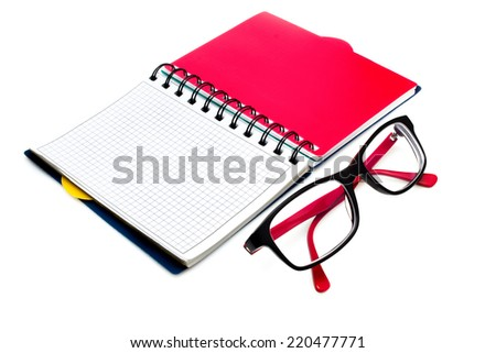 Black glasses and notebook isolated on white - stock photo