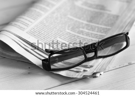 Black glasses on a daily newspaper.