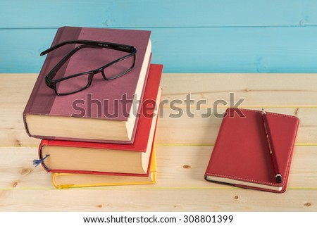 Black glasses on books with a pencil and notebook.  - stock photo