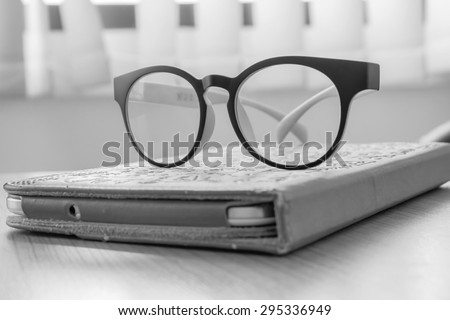 Black glasses placed on Taplet Brown in office made with black and white color.
