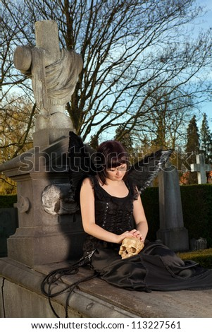Black gothic angel sitting on a grave holding a skull