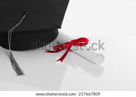 Black Graduation Cap with Degree Isolated on White Background - stock photo