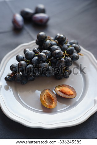 black grapes and plums with a stone on the gray plate - stock photo