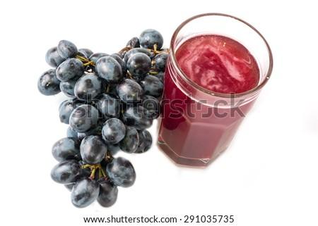 black grapes glass of grape juice white background - stock photo