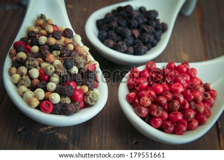 Black, green and pink pepper in white spoon on a wooden table - stock photo