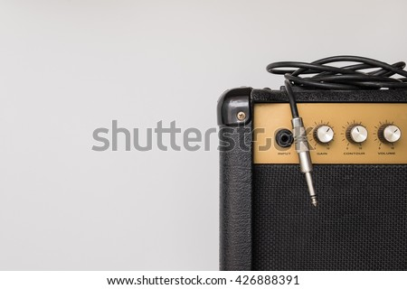 Black guitar amplifier with jack cable on white  background - stock photo