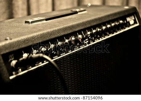 black guitar amplifier with switches and knobs - stock photo