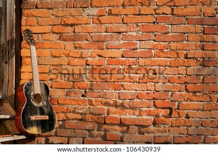 black guitar on the steps with brick background horizontal - stock photo