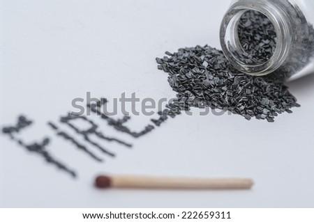 Black gunpowder on white background with word fire written from gun powder and a match stick shallow DOF - stock photo