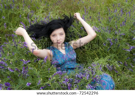Black Hair Girl in blue flowers field - stock photo