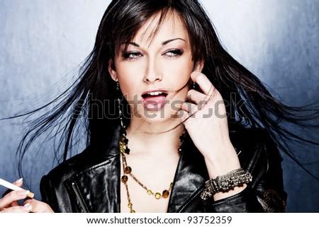 black hair woman in leather jacket, studio shot - stock photo