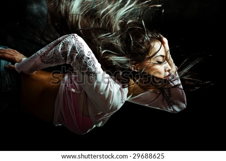 black hair woman with flying hair. studio dark